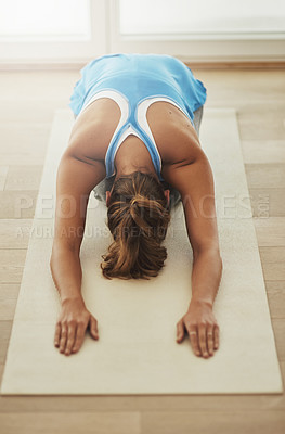 Buy stock photo High angle shot of a young woman practicing yoga at home