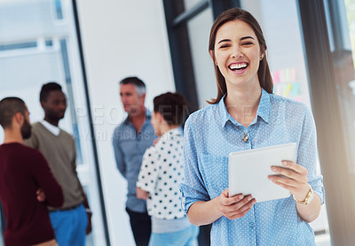 Buy stock photo Cropped portrait of a young businesswoman working in the office with her colleagues in the background