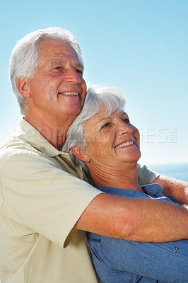 Buy stock photo Senior couple smiling and looking away while standing against sky with man embracing woman from behind