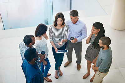 Buy stock photo High angle shot of businesspeople talking in the lobby of their office