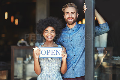 Buy stock photo Portrait of two proud coffee shop owners holding up a sign on opening day