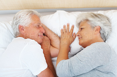Buy stock photo Closeup of senior couple lying on bed and looking at each other