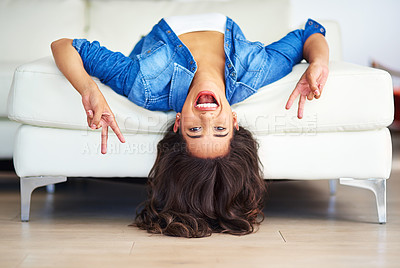 Buy stock photo Shot of a young woman showing the peace sign while lying upside down on her sofa