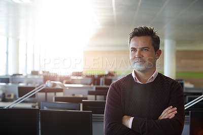 Buy stock photo Shot of a businessman standing with his arms folded in his office