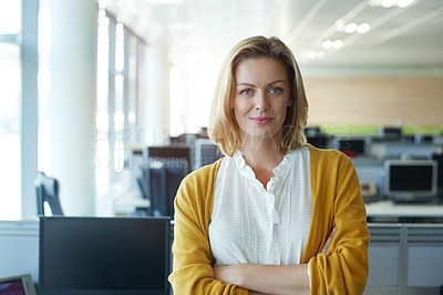 Buy stock photo Portrait of a businesswoman standing with her arms folded in the office