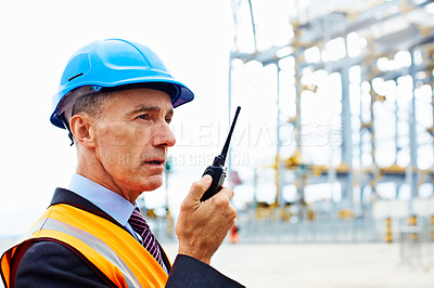 Buy stock photo Shot of a man in workwear standing outside on a large commercial dock talking on a walkie talking
