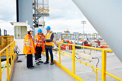 Buy stock photo Shot of three workers talking together over a digital tablet while standing on a commercial dock