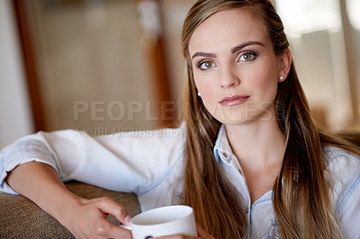 Buy stock photo Shot of an attractive young woman relaxing on her home with a cup of coffee