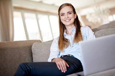 Buy stock photo Shot of an attractive young woman using her laptop while relaxing at home