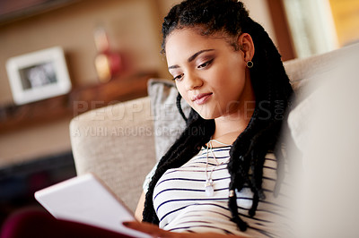 Buy stock photo Shot of a young woman using her tablet while relaxing at home