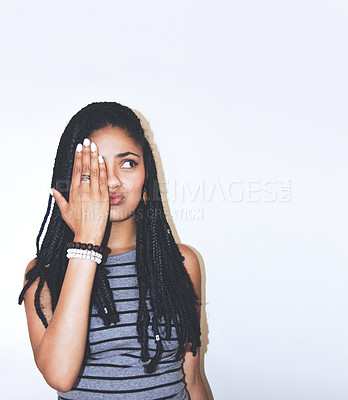 Buy stock photo Studio shot of an attractive young woman with her hand over one eye
