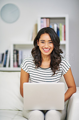 Buy stock photo Cropped portrait of a young woman using her laptop while relaxing on her sofa at home