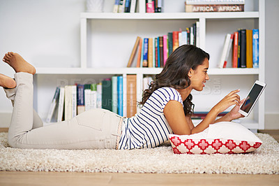Buy stock photo Full length shot of a young woman using her tablet while relaxing at home