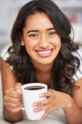 Buy stock photo Cropped portrait of a young woman drinking coffee while relaxing on her sofa at home