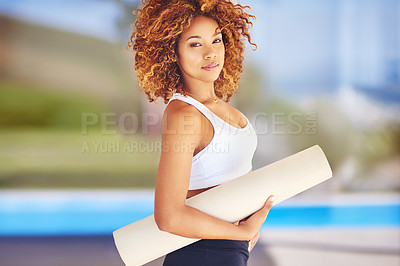 Buy stock photo Cropped shot of a sporty young woman holding her yoga mat