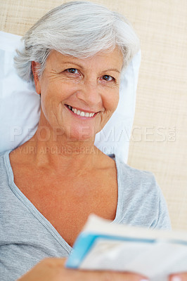 Buy stock photo Closeup portrait of smiling senior woman relaxing on bed and reading a book
