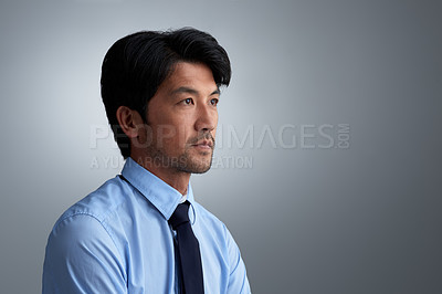 Buy stock photo Studio shot of an ambitious businessman against a gray background