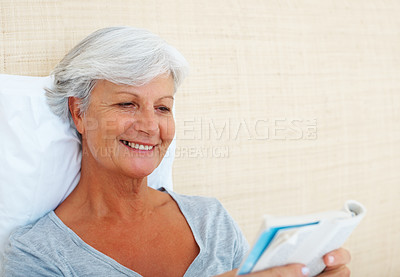Buy stock photo Closeup of senior woman reading a novel in bed and smiling