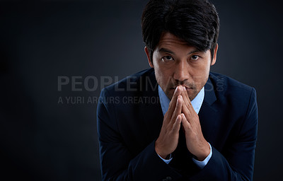 Buy stock photo Studio shot of a businessman with his hands together in gesture against a dark background
