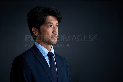 Buy stock photo Studio shot of an ambitious businessman against a dark background