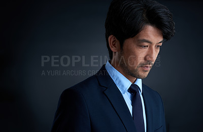 Buy stock photo Studio shot of a thoughtful businessman against a dark background