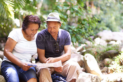 Buy stock photo Cropped shot of a mature couple looking at a map while hiking in a forest
