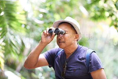 Buy stock photo Cropped shot of a mature man looking through his binoculars while hiking in a forest