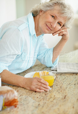 Buy stock photo Portrait of a senior woman having breakfast on the kitchen counter
