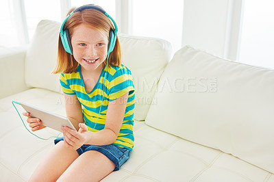 Buy stock photo Shot of a little girl using a digital tablet with headphones at home