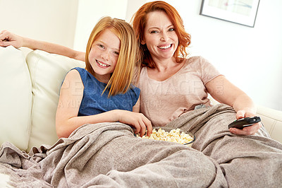 Buy stock photo Shot of a mature woman and her young daughter watching a movie and eating popcorn on the sofa