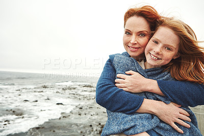 Buy stock photo Shot of a mature woman embracing her young daughter at the waterfront