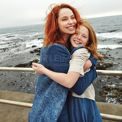 Buy stock photo Shot of a mature woman and her young daughter at the waterfront