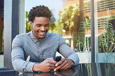 Buy stock photo Shot of a young man using his phone at a sidewalk cafe