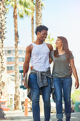 Buy stock photo Shot of a happy young couple going for a walk through the city