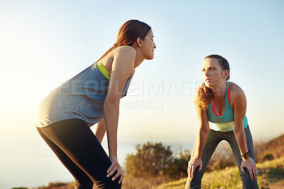 Buy stock photo Shot of two friends taking a breather while out for a run