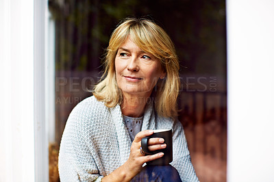 Buy stock photo Shot of a mature woman drinking coffee while looking out of her living room window