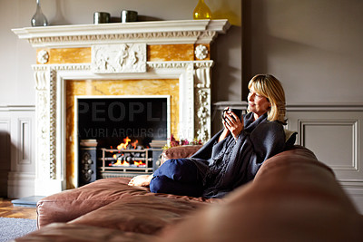 Buy stock photo Shot of a mature woman relaxing on her living room sofa with a fire glowing in the background