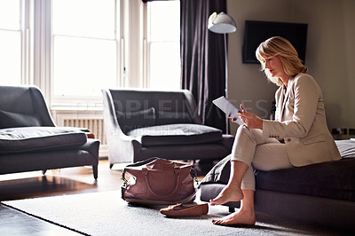 Buy stock photo Shot of a mature businesswoman sitting on a hotel bed using a digital tablet