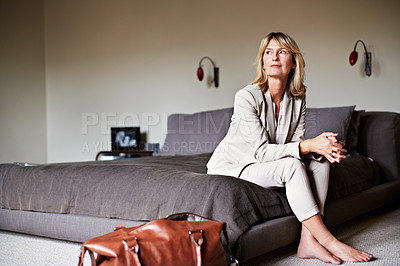 Buy stock photo Shot of a mature businesswoman sitting on hotel bed with her bags