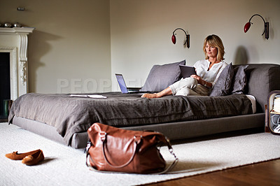 Buy stock photo Shot of a mature businesswoman lying on a hotel bed using a digital tablet