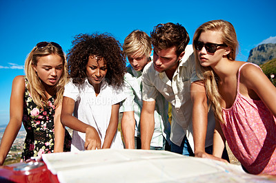 Buy stock photo Shot of a group of friends looking at a map while on a road trip