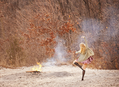 Buy stock photo Shot of a young woman dancing by a fire outdoors in winter