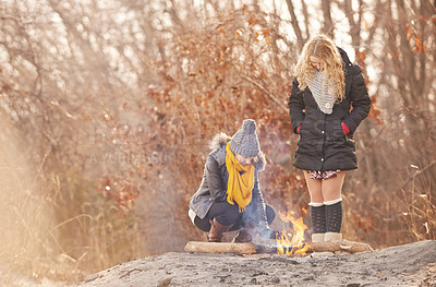 Buy stock photo Shot of two women making a fire outdoors in winter