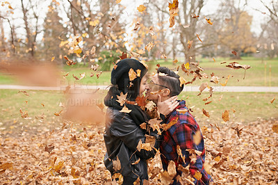 Buy stock photo Shot of a young couple sharing a romantic kiss in the park on an autumn day