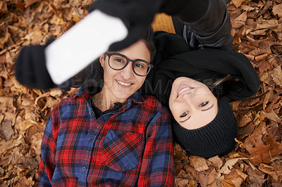 Buy stock photo Shot of a happy young couple taking a selfie on an autumn day in the park