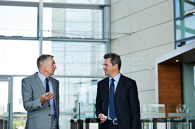 Buy stock photo Shot of two businessman talking together while walking through an office building lobby
