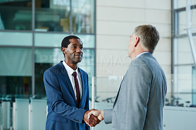 Buy stock photo Shot of two businessmen shaking hands together in the lobby of an office building