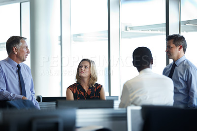 Buy stock photo Shot of a group of businesspeople talking together in the office