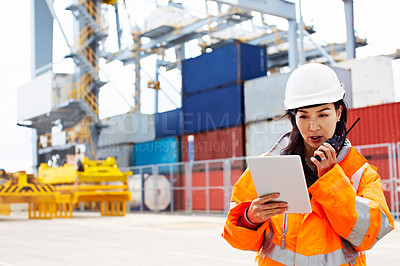 Buy stock photo Shot of a woman in workwear talking on a walkie talkie while standing on a commercial dock