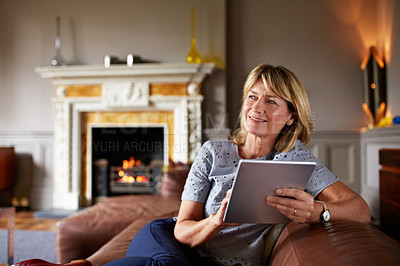 Buy stock photo Shot of a mature woman sitting on her sofa using a digital tablet with a fire glowing in the background